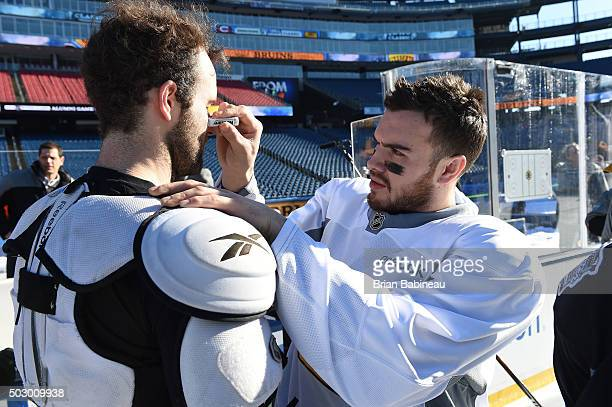Zac Rinaldo of the Boston Bruins applies eyeblack under a teammate's face before practice as part of the 2016 Bridgestone NHL Classic at Gillette...