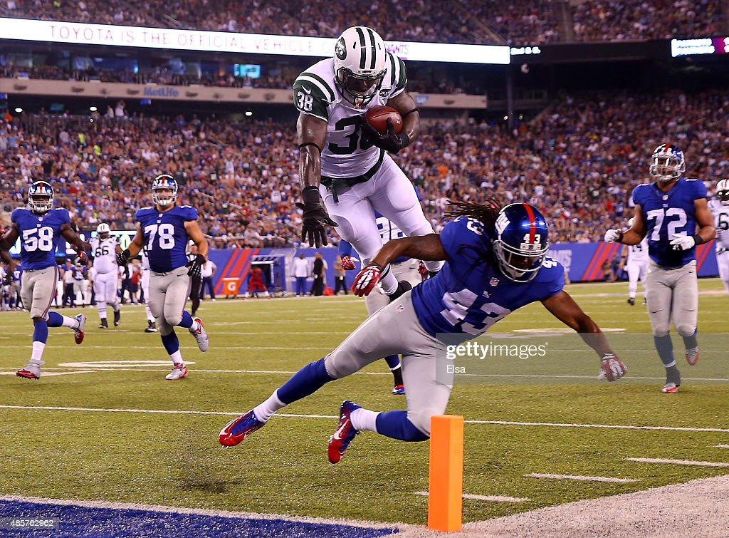 Zac Stacy #38 of the New York Jets jumps over Brandon Meriweather #43 of the New York Giants to score a touchdown in the second quarter during preseason action at MetLife Stadium on August 29, 2015 in East Rutherford, New Jersey.