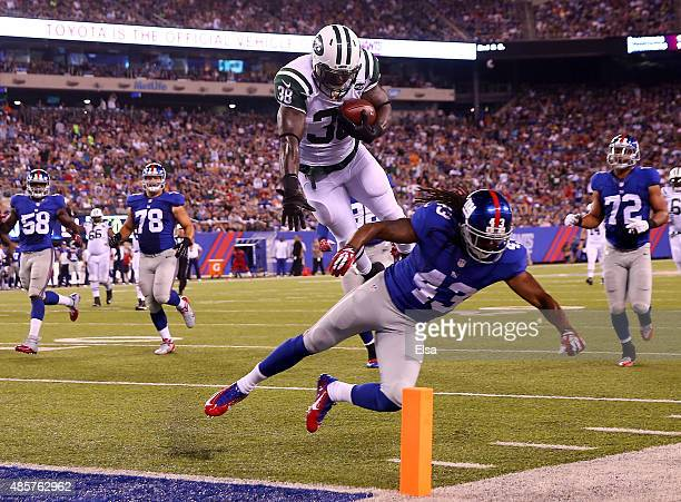 Zac Stacy of the New York Jets jumps over Brandon Meriweather of the New York Giants to score a touchdown in the second quarter during preseason...
