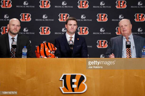 Zac Taylor looks on along with Cincinnati Bengals director of player personnel Duke Tobin and owner Mike Brown after being introduced as the new head...