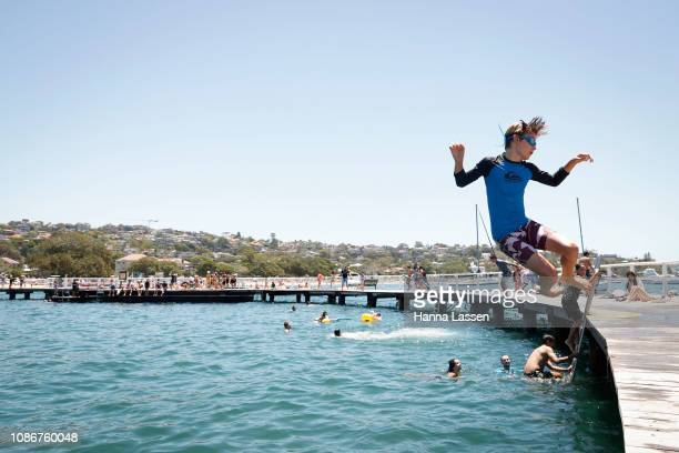 Zac Von Arnim jumps to the water at Balmoral Beach on December 26 2018 in Sydney Australia Sydney residents are enjoying a hot Christmas break with...