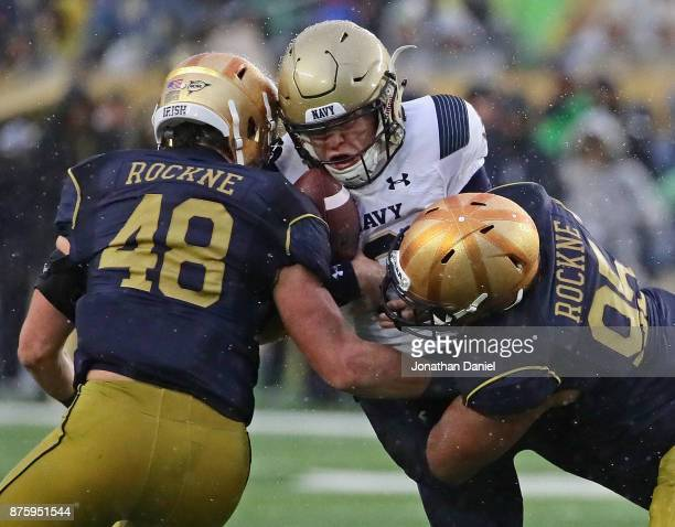 Zach Abey of the Navy Midshipmen is hit by Greer Martini and Myron TagovailoaAmosa of the Notre Dame Fighting Irish at Notre Dame Stadium on November...