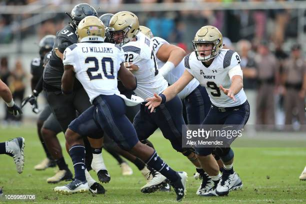 Zach Abey of the Navy Midshipmen tosses the ball to CJ Williams of the Navy Midshipmen during a game against the UCF Knights at Spectrum Stadium on...
