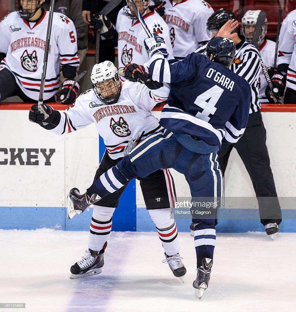 Zach Aston-Reese #12 of the Northeastern Huskies checks Rob O'Gara #4 of the Yale Bulldogs during NCAA hockey at Matthews Arena on January 6, 2015 in Boston, Massachusetts. The Huskies won 3-2.