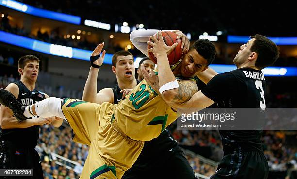 Zach Auguste of the Notre Dame Fighting Irish and Alex Barlow of the Butler Bulldogs go after the ball in the second half during the third round of...