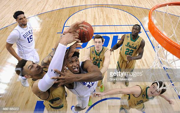 Zach Auguste of the Notre Dame Fighting Irish and Justise Winslow of the Duke Blue Devils go after the ball during the semifinals of the 2015 ACC...
