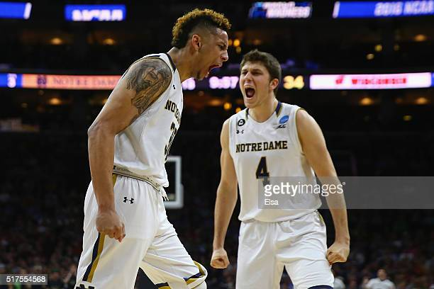 Zach Auguste of the Notre Dame Fighting Irish celebrates with teammate Matt Ryan after a basket in the second half against the Wisconsin Badgers...