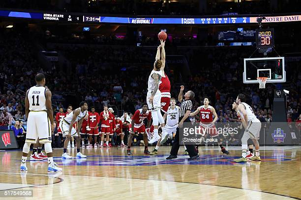 Zach Auguste of the Notre Dame Fighting Irish jumps for the ball against Ethan Happ of the Wisconsin Badgers to start the game during the 2016 NCAA...