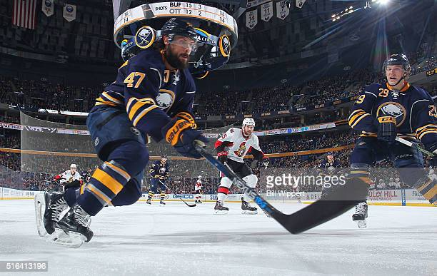 Zach Bogosian and Jake McCabe of the Buffalo Sabres converge on the puck against the Ottawa Senators during an NHL game on March 18 2016 at the First...