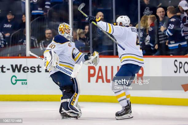 Zach Bogosian of the Buffalo Sabres celebrates with goaltender Carter Hutton following a 21 shootout victory over the Winnipeg Jets at the Bell MTS...