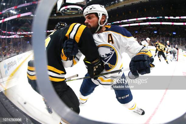 Zach Bogosian of the Buffalo Sabres checks Danton Heinen of the Boston Bruins into he boards in the first period of the game between the Boston...
