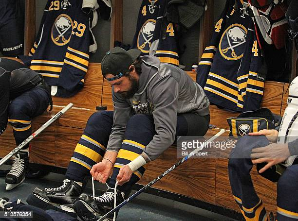 Zach Bogosian of the Buffalo Sabres laces his skates before playing the Calgary Flames in an NHL game on March 3 2016 at the First Niagara Center in...