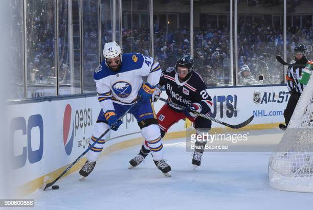 Zach Bogosian of the Buffalo Sabres plays the puck behind the net as Jimmy Vesey of the New York Rangers pursues the play during the 2018 Bridgestone...