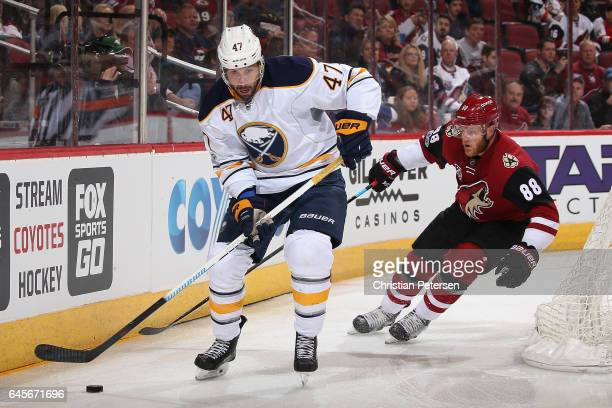 Zach Bogosian of the Buffalo Sabres skates with the puck ahead of Jamie McGinn of the Arizona Coyotes during the first period of the NHL game at Gila...