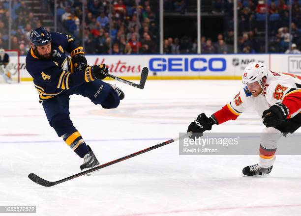 Zach Bogosian of the Buffalo Sabres takes a shot as Sam Bennett of the Calgary Flames defends during the second period at the KeyBank Center on...