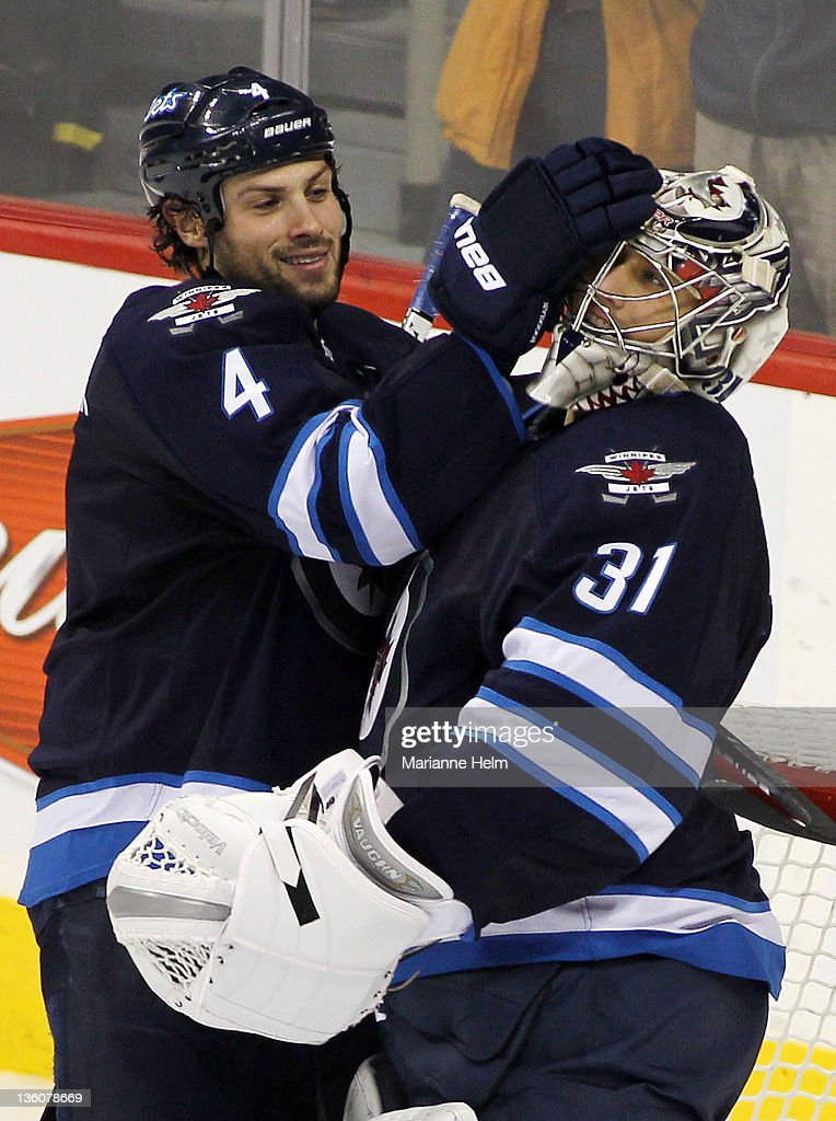 Zach Bogosian #4 of the Winnipeg Jets celebrates with goalie Ondrej Pavelec #31 after the Jets defeated the Montreal Canadiens in NHL action at the MTS Centre on December 22, 2011 in Winnipeg, Manitoba, Canada.