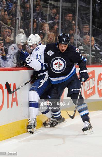 Zach Bogosian of the Winnipeg Jets checks Tom Pyatt of the Tampa Bay Lightning into the boards during first period action at the MTS Centre on April...