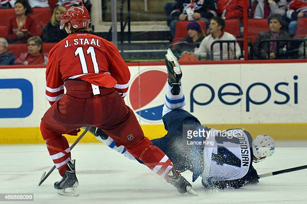 Zach Bogosian of the Winnipeg Jets falls while defending Jordan Staal of the Carolina Hurricanes at PNC Arena on February 4 2013 in Raleigh North...