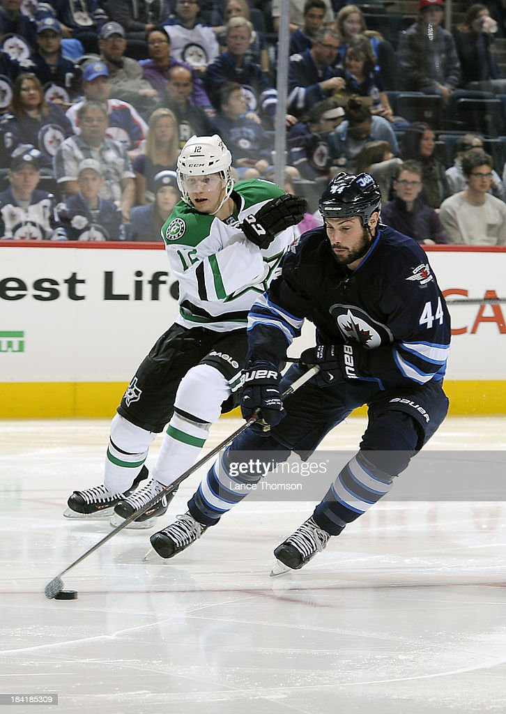 Zach Bogosian #44 of the Winnipeg Jets plays the puck away from Alex Chiasson #12 of the Dallas Stars during third period action at the MTS Centre on October 11, 2013 in Winnipeg, Manitoba, Canada.