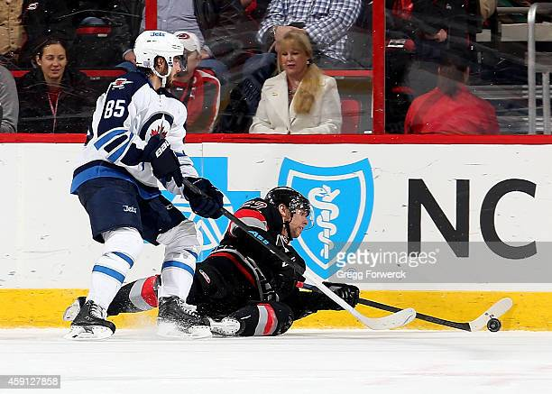 Zach Boychuck of the Carolina Hurricanes attempts to advance the puck from the ice ahead of Mathieu Perreault of the Winnipeg Jets during their NHL...