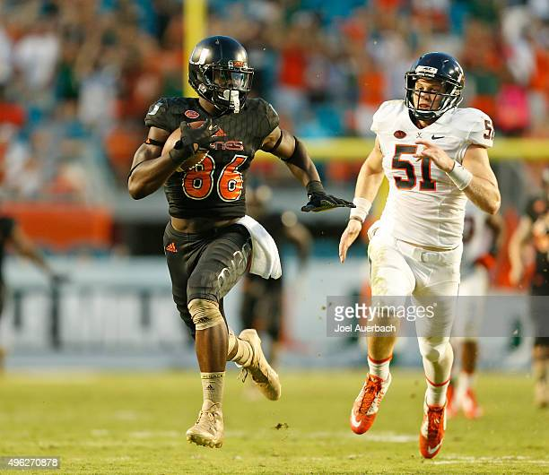 Zach Bradshaw of the Virginia Cavaliers pursues David Njoku of the Miami Hurricanes as he runs with the ball on November 7 2015 at Sun Life Stadium...