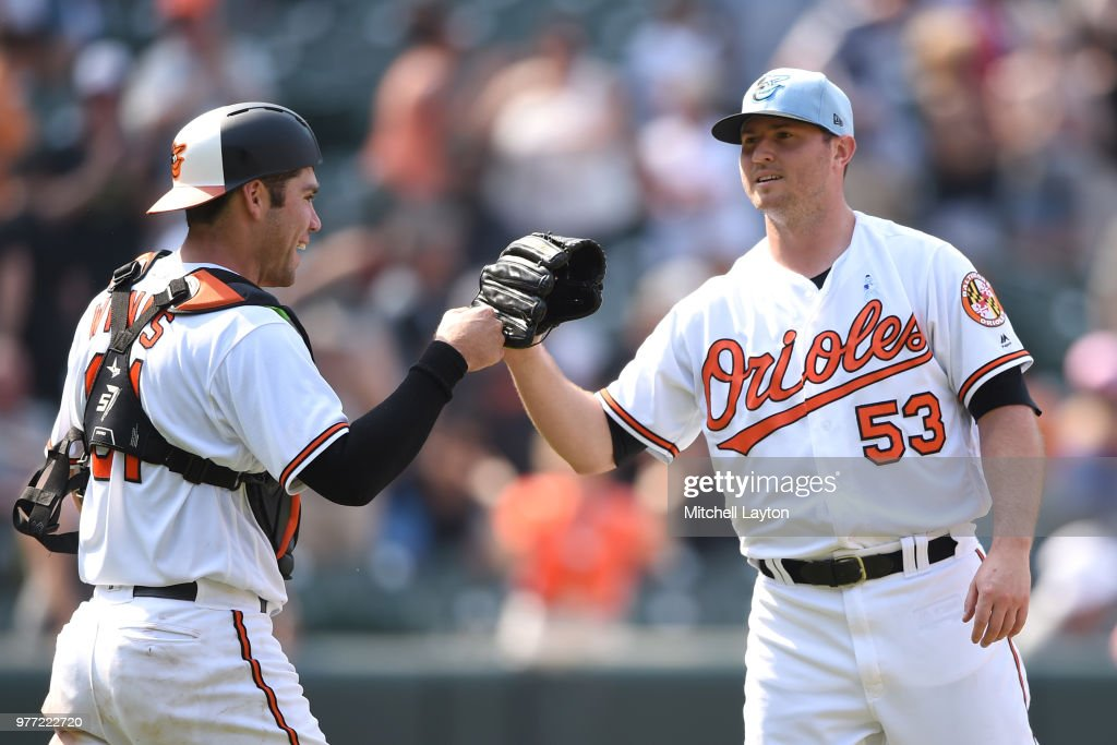 Zach Britton #53 of the Baltimore Orioles celebrates a win with Austin Wynns #61 after a baseball game against the Miami Marlins at Oriole Park at Camden Yards on June 17, 2018 in Baltimore, Maryland.
