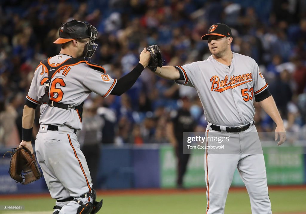 Zach Britton #53 of the Baltimore Orioles celebrates their victory with Caleb Joseph #36 during MLB game action against the Toronto Blue Jays at Rogers Centre on September 13, 2017 in Toronto, Canada.