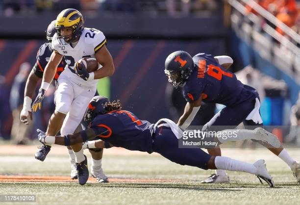 Zach Charbonnet of the Michigan Wolverines runs the ball as Stanley Green of the Illinois Fighting Illini dives for the tackle during the first half...