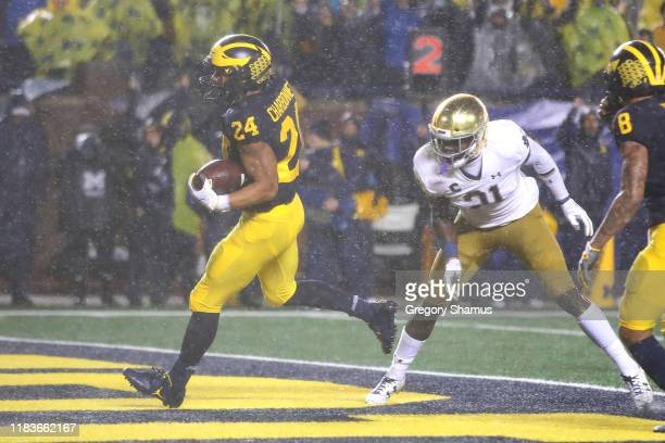 Zach Charbonnet of the Michigan Wolverines scores a first half touchdown past Jalen Elliott of the Notre Dame Fighting Irish at Michigan Stadium on...