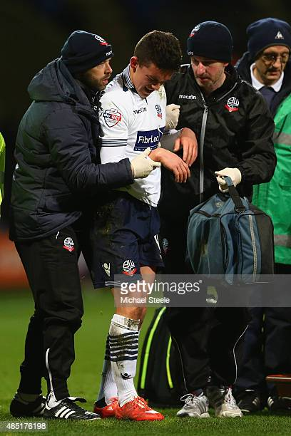 Zach Clough of Bolton is helped by medical staff after injuring his elbow during the Sky Bet Championship match between Bolton Wanderers and Reading...