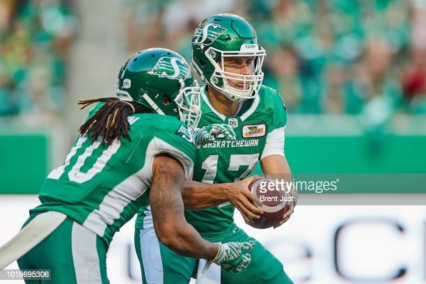 Zach Collaros fakes a handoff to Tre Mason of the Saskatchewan Roughriders in the game between the Calgary Stampeders and Saskatchewan Roughriders at...
