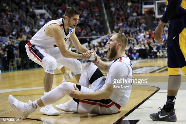 Zach Collins helps up Przemek Karnowski of the Gonzaga Bulldogs against the West Virginia Mountaineers during the 2017 NCAA Men's Basketball...