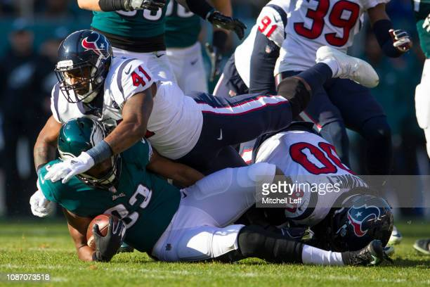 Zach Cunningham and Jadeveon Clowney of the Houston Texans tackle Josh Adams of the Philadelphia Eagles at Lincoln Financial Field on December 23,...
