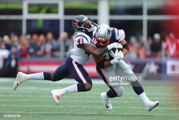Zach Cunningham of the Houston Texans tackles James Develin of the New England Patriots during the first half at Gillette Stadium on September 9,...