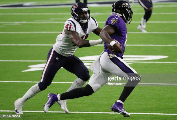 Zach Cunningham of the Houston Texans tackles Lamar Jackson of the Baltimore Ravens during the second half at NRG Stadium on September 20, 2020 in...
