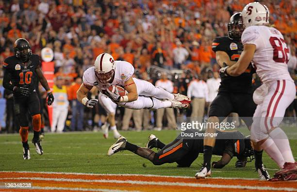 Zach Ertz of the Stanford Cardinal scores a 16-yard touchdown reception in the third quarter against the Oklahoma State Cowboys during the Tostitos...