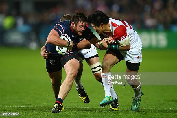 Zach Fenoglio of the United States is tackled by Harumichi Tatekawa of Japan during the 2015 Rugby World Cup Pool B match between USA and Japan at...