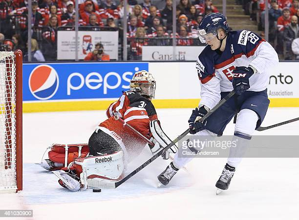 Zach Fucale of Team Canada makes a big save against Pavol Skalicky of Team Slovakia during a semifinal game in the 2015 IIHF World Junior Hockey...
