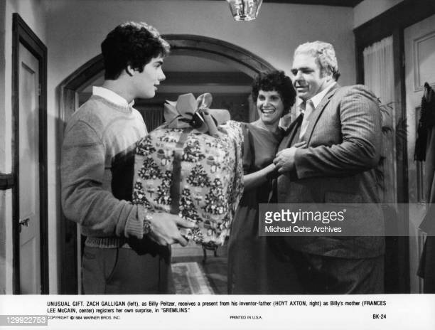 Zach Galligan gives Frances Lee McCain and Hoyt Axton a gift in a scene from the film 'Gremlins' 1984