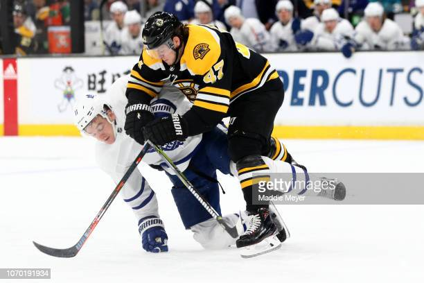 Zach Hyman of the Toronto Maple Leafs and Torey Krug of the Boston Bruins battle for control of the puck during the second period of the game between...