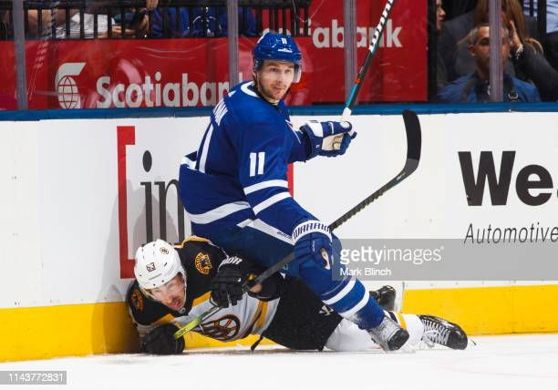 Zach Hyman of the Toronto Maple Leafs battles with Brad Marchand of the Boston Bruins during the third period during Game Four of the Eastern...