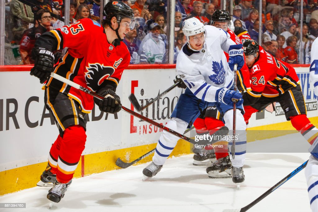 Zach Hyman #11 of the Toronto Maple Leafs clears the puck from Sean Monahan #23 of the Calgary Flames in an NHL game against the Toronto Maple Leafs at the Scotiabank Saddledome on November 28, 2017 in Calgary, Alberta, Canada.