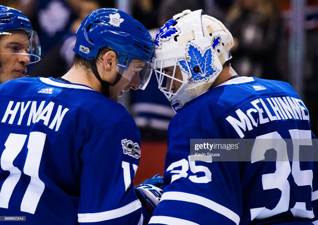 Zach Hyman #11 of the Toronto Maple Leafs congratulates teammate Curtis McElhinney #35 after the Leafs defeated the Edmonton Oilers at the Air Canada Centre on December 10, 2017 in Toronto, Ontario, Canada.