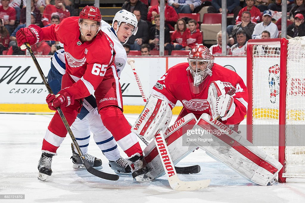 Zach Hyman #11 of the Toronto Maple Leafs fights for position with Danny DeKeyser #65 of the Detroit Red Wings next to goaltender Petr Mrazek #34 of the Wings during an NHL game at Joe Louis Arena on January 25, 2017 in Detroit, Michigan.