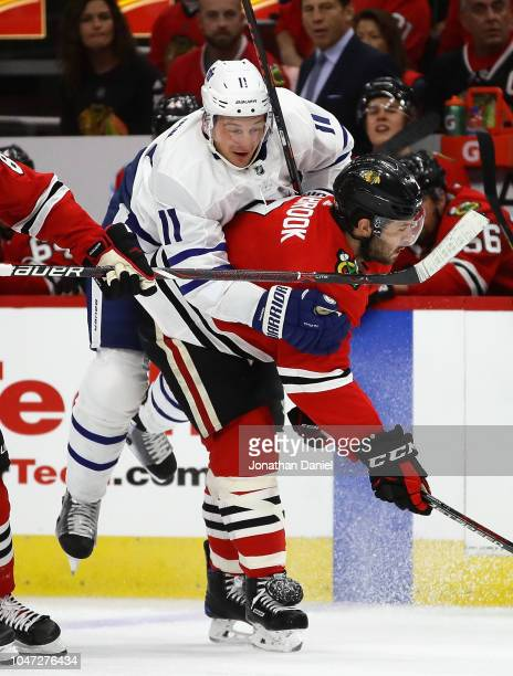 Zach Hyman of the Toronto Maple Leafs rides the back of Brent Seabrook of the Chicago Blackhawks after a collision during the regular seasopn opening...