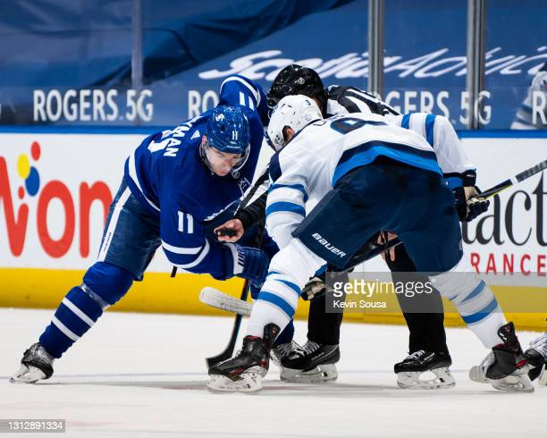 Zach Hyman of the Toronto Maple Leafs takes a face off against Neal Pionk of the Winnipeg Jets during the second period at the Scotiabank Arena on...