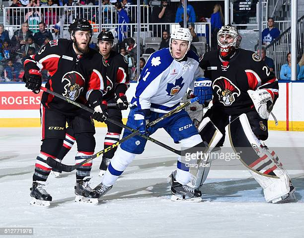 Zach Hyman of the Toronto Marlies fights for crease space with Fredrik Claesson Michael Sdao and goalie Matt O'Connor of the Binghamton Senators...