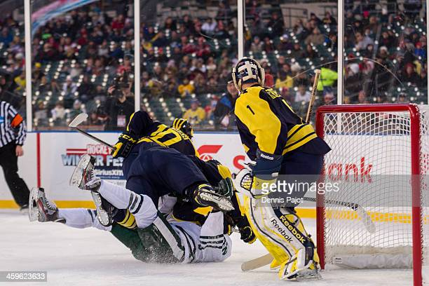 Zach Hymen of the Michigan Wolverines lays a massive hit on Lee Reimer of the Michigan State Spartans on December 28 2013 at Comerica Park in Detroit...