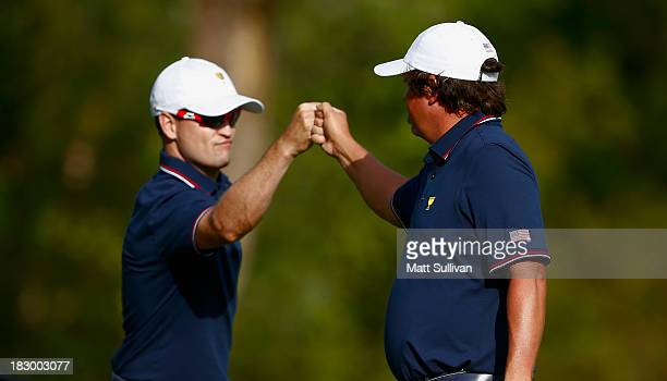 Zach Johnson and Jason Dufner of the U.S. Team celebrate a birdie on the ninth hole during the Day One Four-Ball Matches at the Muirfield Village...