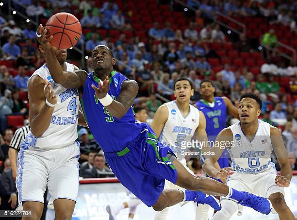 Zach Johnson of the Florida Gulf Coast Eagles dives to shoot the ball in the first half against Isaiah Hicks of the North Carolina Tar Heels during...